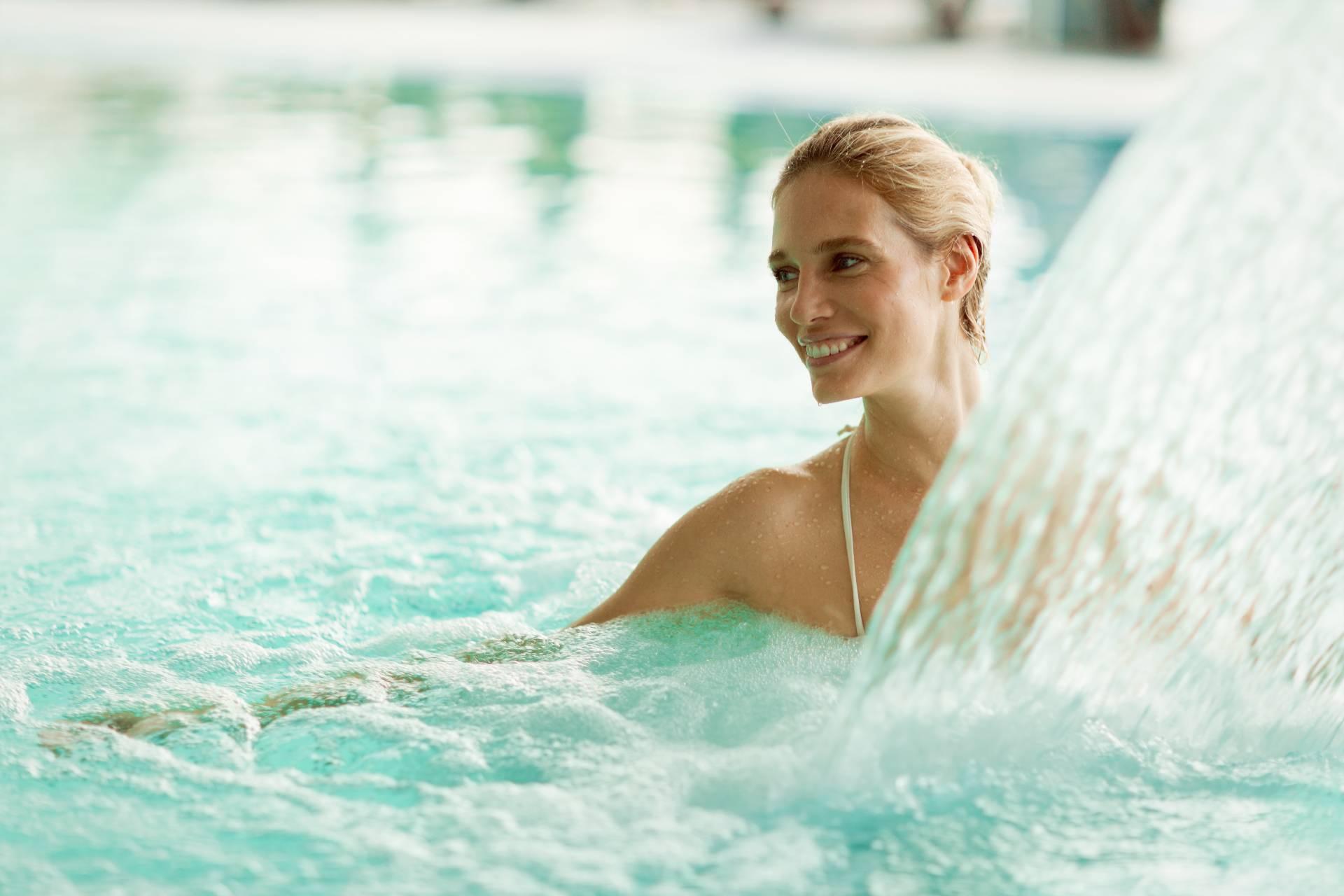 Beautiful woman enjoying jet of water in spa resort